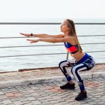 blonde beautiful girl doing squats during workout on the quay near the sea 8353 6945 150x150 - sporty girl squats with barbell training