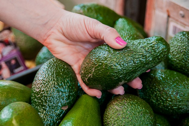 cropped image of a customer choosing avocados in the supermarket close up of woman hand holding avocado in market sale shopping food consumerism and people concept 1391 641 - Trend s názvom avokádo – je naozaj také zdravé?