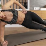full shot woman doing side plank 150x150 - Faceless curly woman suffers from spine pain, has injury after overtraining, wears sport bra, shows location of inflammation, leads sporty lifestyle, isolated on white background. Chronic disease