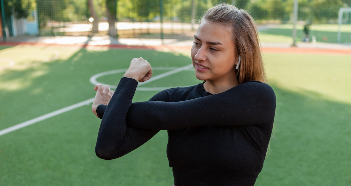 young slim fit woman sportswear doing pre training warm up hand stretching stadium healthy lifestyle concept outdoor training - 3 fakty a mýty o strečingu